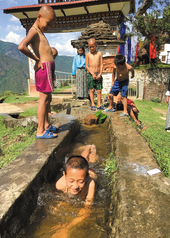 僧侶学校付近の水路で水遊びに興じる子どもたち。